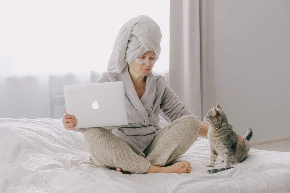 A woman sitting on a bed with a cat