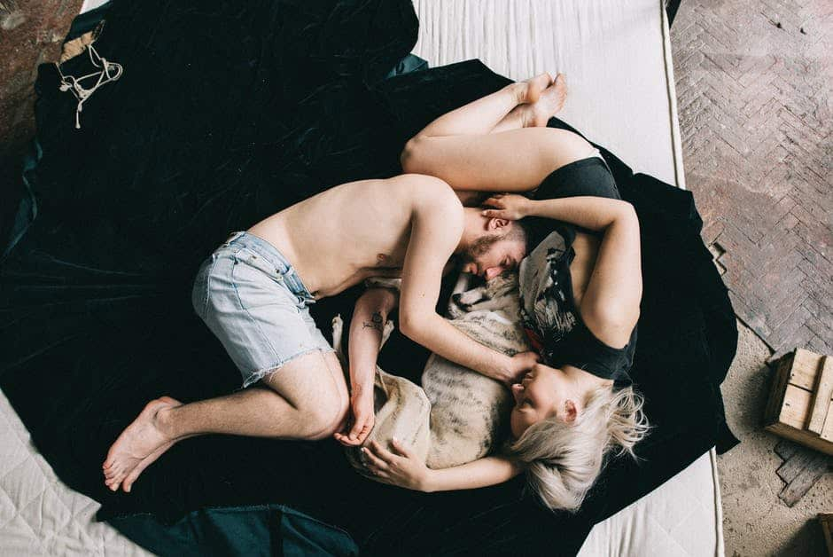 Couple lying in bed with a dog