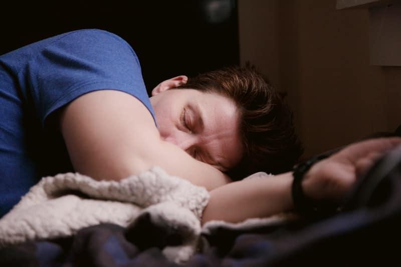 A young boy sleeping on a bed